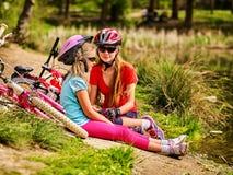 La bicicleta de los niños tiene resto cerca del agua en el parque al aire libre Fotos de archivo