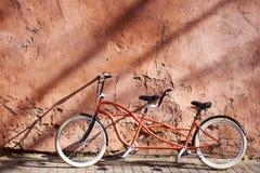 La bicicleta doble en t?ndem se inclin? contra la pared agrietada el d?a soleado Concepto del transporte y el viajar imágenes de archivo libres de regalías