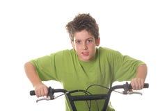 La bicicleta joven del montar a caballo del muchacho ayuna Imagen de archivo libre de regalías