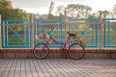 La bicicleta roja vieja con las cestas se coloca en la cerca en la puesta del sol foto de archivo