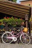 La bicicleta rosada parqueada adorna el interior Imagen de archivo