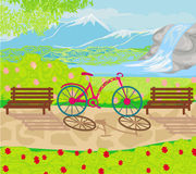 La bicicleta se coloca en el parque entre los bancos Imagen de archivo