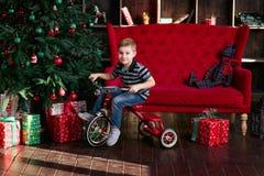 La bicicleta sonriente del montar a caballo del niño pequeño en el cuarto con el árbol de navidad, Año Nuevo presenta, coche rojo Imagenes de archivo