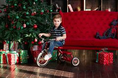 La bicicleta sonriente del montar a caballo del niño pequeño en el cuarto con el árbol de navidad, Año Nuevo presenta, coche rojo Imágenes de archivo libres de regalías