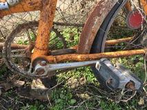 La bicicleta vieja sola con un marco anaranjado en una hierba, mohos en una cerca fotografía de archivo