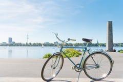 La bicicletta blu d'annata ha parcheggiato a lakeshore del lago Alster a Amburgo Immagine Stock