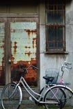La bicicletta d'annata con il canestro ha parcheggiato in marciapiede accanto al arrugginito Immagine Stock