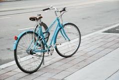 La bicicletta delle donne parcheggiata sulla via Fotografie Stock