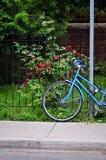 La bicicletta delle donne parcheggiata sulla via Fotografia Stock Libera da Diritti