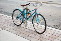 La bicicletta delle donne parcheggiata sulla via Immagini Stock
