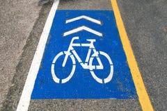 La bicicletta e la freccia bianche firmano sulla strada blu del fondo Fotografia Stock Libera da Diritti