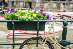 La bicicletta ha parcheggiato sul ponte con i fiori a Amsterdam Olanda fotografie stock