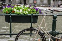 La bicicletta ha parcheggiato sul ponte con i fiori a Amsterdam Olanda immagini stock libere da diritti