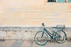 La bicicletta verde parcheggiata, si appoggia la parete e la finestra concrete di lerciume del vecchio mattone colore d'annata, s Immagini Stock