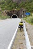 La bicyclette avec le bagage se tient devant un tunnel, Lofoten, Nordl images stock