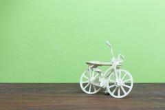 La bicyclette en bois joue sur le vieux bois et le fond vert de mur Image libre de droits
