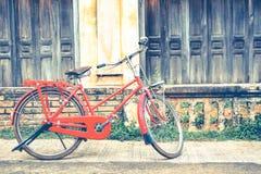 La bicyclette rouge de hippie dans le vieux bâtiment mure le fond Image stock