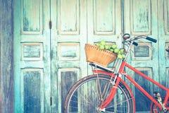 La bicyclette rouge de hippie dans le vieux bâtiment mure le fond Photos stock
