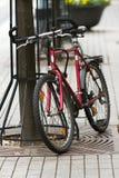La bicyclette rouge s'est garée sur la rue à Vilnius Photo stock