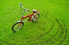 La bicyclette rouge sur l'herbe photographie stock libre de droits
