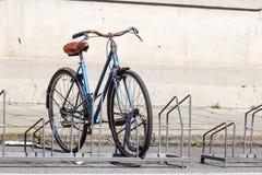 La bicyclette s'est garée dans la rue sur le support de bicyclette Image stock