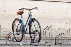 La bicyclette s'est garée dans la rue sur le support de bicyclette Photos stock