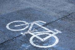 La bicyclette se connectent la dalle en béton d'asphalte en parc montré que ce secteur est pour le stationnement de bicyclette Image libre de droits