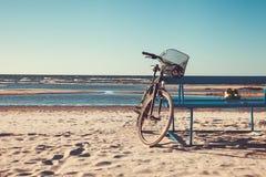 La bicyclette se tient près du banc sur la plage contre la mer Photo stock