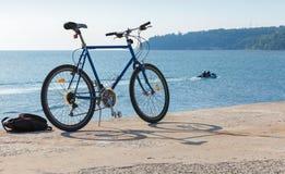 La bicyclette se tient sur la jetée, côte de la Mer Noire Image stock