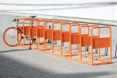 La bicyclette se tient sur le parc orange de bicyclette Images stock