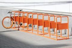 La bicyclette se tient sur le parc orange de bicyclette Images stock