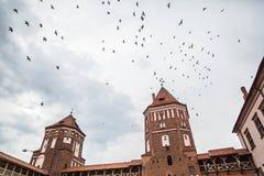 La Bielorussia, uccelli sopra Mir Castle un giorno nuvoloso fotografia stock libera da diritti