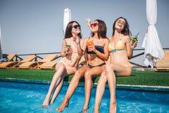 la Bien-estructura y los modelos emocionados se sientan en el borde de la piscina Sostienen los cócteles en manos Mirada de las m fotografía de archivo libre de regalías