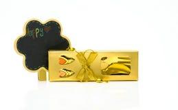 La bifurcación y la cuchara en oro encajonan los cubiertos con los ornamentos y la tarjeta de la pizarra en el fondo blanco Fotos de archivo libres de regalías