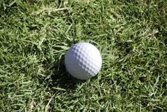 La bille de golf se situe dans la longue herbe dans le rugueux Photos stock