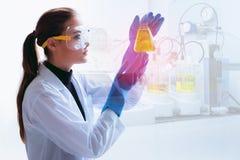 La bio- tecnologia del ricercatore sta esaminando la reazione chimica in bea immagini stock