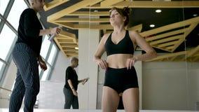 La bionda caucasica in pantaloni a strisce spalma gli sport lubrifica castana in una stanza bianca video d archivio
