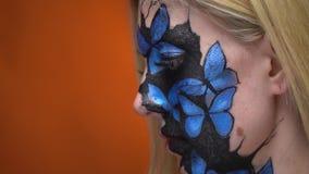 La bionda con la vernice di carrozzeria sul suo fronte sotto forma di farfalle blu esamina il suo amico video d archivio