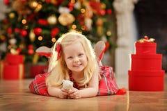 La bionda del bambino della ragazza in un vestito rosso accanto all'albero di Natale è dentro Fotografia Stock
