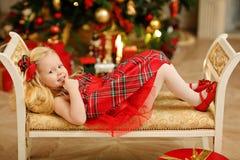La bionda del bambino della ragazza in un vestito rosso accanto all'albero di Natale è dentro Fotografie Stock
