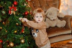 La bionda del neonato in maglione beige si agghinda l'albero di Natale, caduta Immagine Stock