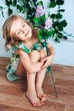 La bionda della bambina si siede sul pavimento con un fiore in sua mano in una stanza, negli occhi chiusi e nei sorrisi fotografia stock