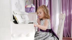 La bionda della ragazza gioca il piano, ragazza in un vestito con una cinghia porpora archivi video