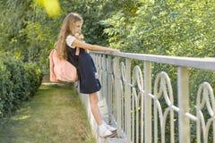 La bionda della scolara della ragazza con lo zaino in uniforme scolastico vicino recinta il cortile della scuola immagine stock libera da diritti