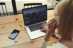 La bionda dello studente sta sedendosi ad un computer portatile in un caffè Fotografia Stock