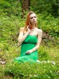 La bionda emozionale, carte del gioco, getta le carte sull'erba, seria Fotografia Stock