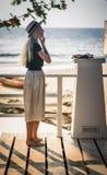La bionda in gonna lunga che sta sul ponte di legno sui precedenti del mare di mattina e regola i suoi orecchini a Immagini Stock