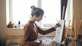 La bionda graziosa sta dipingendo i bei fiori su tela che lavora nello studio da solo che sta davanti al cavalletto con la spazzo archivi video