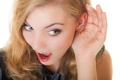 La bionda ha sorpreso la ragazza del gossip con la mano dietro il segreto d'ascolto dell'orecchio Fotografie Stock