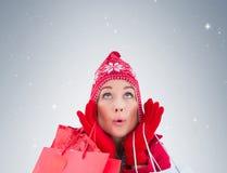 La bionda nell'inverno copre i sacchetti della spesa della tenuta Fotografia Stock